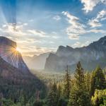 sun shining through some mountains